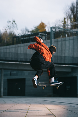 Photo pour skateboarder in red jacket performing jump trick in urban location - image libre de droit