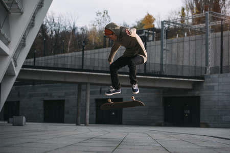Foto de young skateboarder performing jump trick in urban location - Imagen libre de derechos