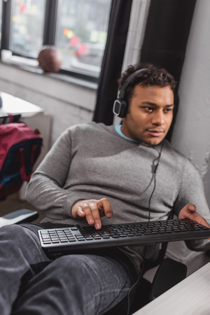 man in headphones typing on keyboard at modern office