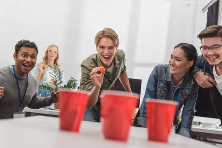 Photo pour young attractive people playing beer pong at modern office after work - image libre de droit