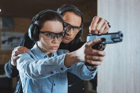 Foto de instructor helping customer in shooting gallery - Imagen libre de derechos
