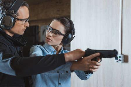 Foto de male instructor helping customer in shooting range - Imagen libre de derechos