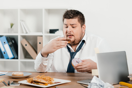 Photo for overweight businessman eating donuts, hamburger and french fries at workplace - Royalty Free Image