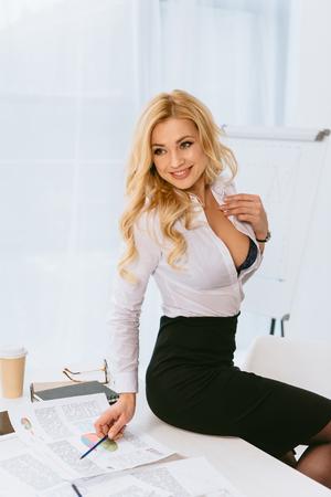 Photo pour sexy woman with unbuttoned shirt sitting on table with pencil - image libre de droit