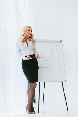 Photo pour seductive blonde businesswoman standing at chart and holding pencil - image libre de droit