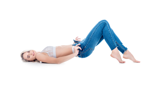 Photo for sexy girl lying and taking off jeans, isolated on white - Royalty Free Image