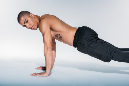 Photo pour african american sportive man doing push up and looking at camera - image libre de droit