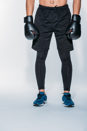 Photo pour Cropped image of boxer in sport shorts and gloves - image libre de droit