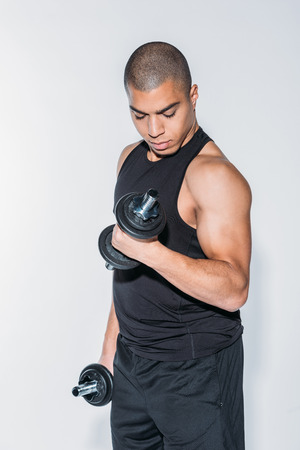 Photo pour african american sportsman exercising with dumbbells isolated on white - image libre de droit