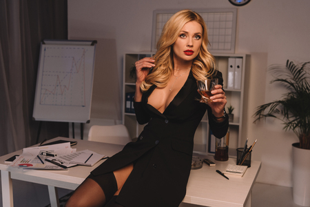 Photo for sexy woman posing with glass of whiskey at office in evening and looking away - Royalty Free Image