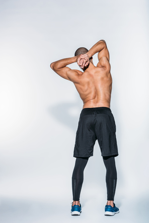 Photo pour rear view of muscular african american sportsman stretching body - image libre de droit