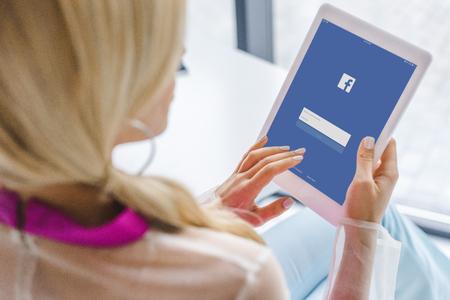 Foto de cropped view of woman using digital tablet with facebook website - Imagen libre de derechos