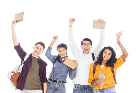 Foto de portrait of cheerful interracial students with backpacks and notebooks isolated on white - Imagen libre de derechos