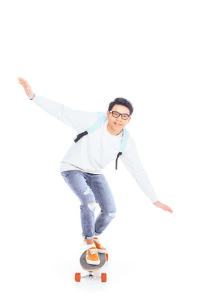 Foto de asian teenager with backpack riding skateboard isolated on white - Imagen libre de derechos