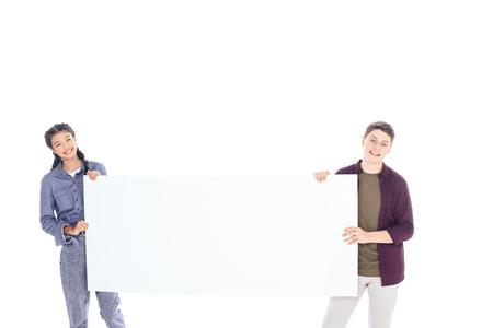 Foto de portrait of smiling teenagers holding empty banner isolated on white - Imagen libre de derechos