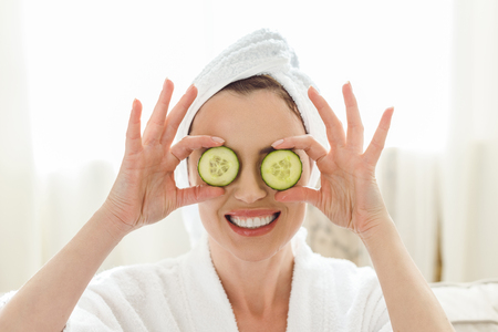 Photo pour smiling woman holding cucumber slices in front of eyes - image libre de droit