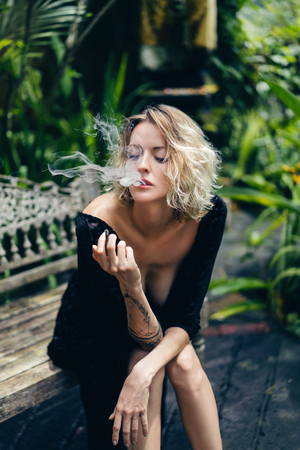 Photo for blond woman in black clothing smoking cigarette while resting on bench on terrace, ubud, bali, indonesia - Royalty Free Image