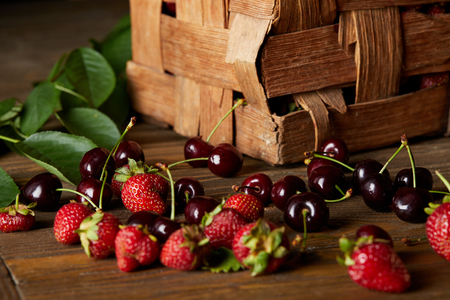 Foto de ripe cherries and strawberries on wooden surface with leaves and rustic box - Imagen libre de derechos