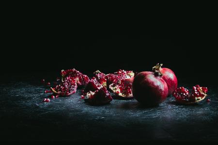 Photo pour pomegranate pieces and seeds on a dark surface - image libre de droit