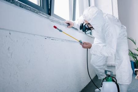Foto de pest control worker spraying chemicals under windowsill at home - Imagen libre de derechos