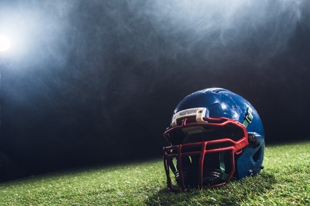 Foto de close-up shot of american football helmet on green grass with white smoke above - Imagen libre de derechos