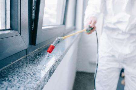 Foto de cropped image of pest control worker spraying pesticides on windowsill at home - Imagen libre de derechos