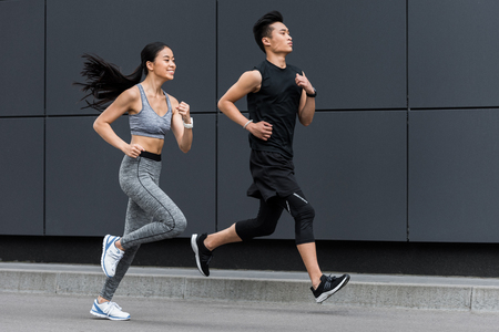 Foto de side view of asian sportsman and sportswoman running at city street - Imagen libre de derechos