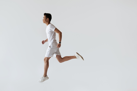 Foto de side view of young asian jogger running on grey background - Imagen libre de derechos