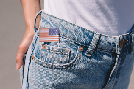 Foto de partial view of woman in jeans with american flagpole in pocket, americas independence day holiday concept - Imagen libre de derechos
