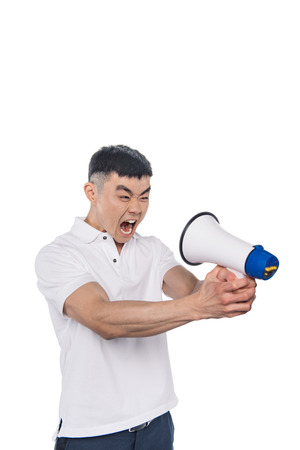Photo pour portrait of yelling asian man looking at bullhorn isolated on white - image libre de droit