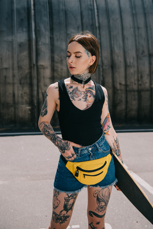 Photo pour young attractive tattooed girl with hand in pocket holding skateboard at street - image libre de droit