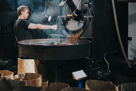 Foto de Man controlling process of roasting coffee beans in traditional machine - Imagen libre de derechos