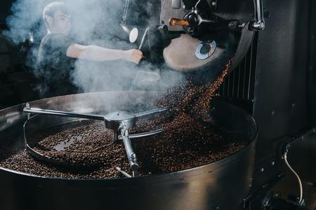 Foto de Professional male roaster loading machine with coffee beans - Imagen libre de derechos