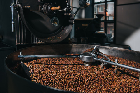 Foto de Interior of coffee production workshop with working coffee roasting machine - Imagen libre de derechos