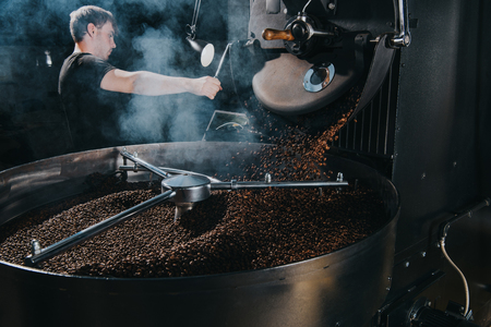 Foto de Professional male roaster loading container of steaming machine with coffee beans - Imagen libre de derechos