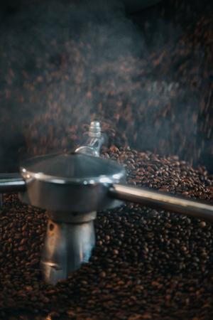 Foto de Steaming hot coffee beans being roasted in professional machine - Imagen libre de derechos