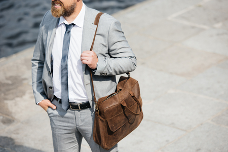 Photo for cropped view of businessman with leather bag walking on quay - Royalty Free Image