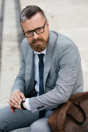 Photo for handsome bearded businessman in grey suit with leather bag and watch - Royalty Free Image