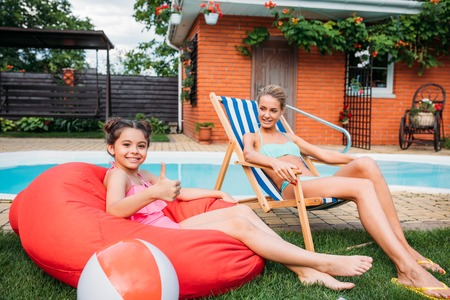 Photo pour mother and smiling daughter resting near swimming pool on backyard on summer day - image libre de droit