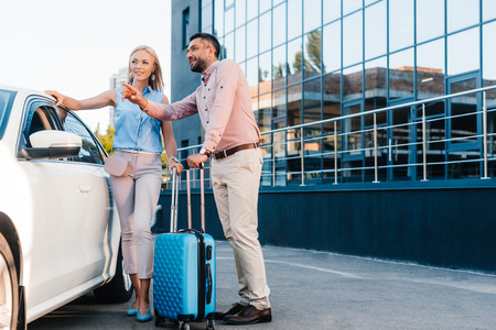 Photo pour husband and wife with baggage standing at car on parking - image libre de droit