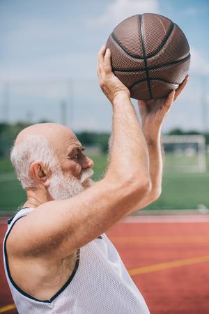 Foto de side view of elderly bearded man with basketball ball in hands - Imagen libre de derechos
