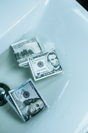 Photo pour top view of dollar banknotes in water in sink - image libre de droit