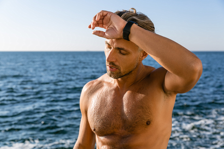 Photo pour tired shirtless adult man wiping sweat from forehead after training on seashore - image libre de droit