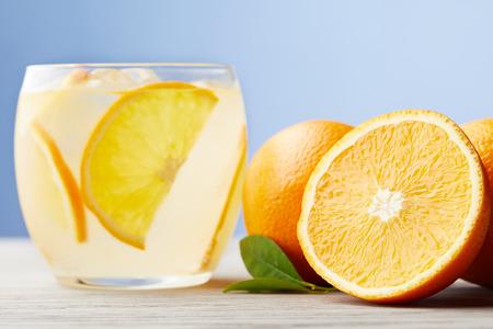 Foto de glass of fresh lemonade with ripe oranges on wooden table - Imagen libre de derechos