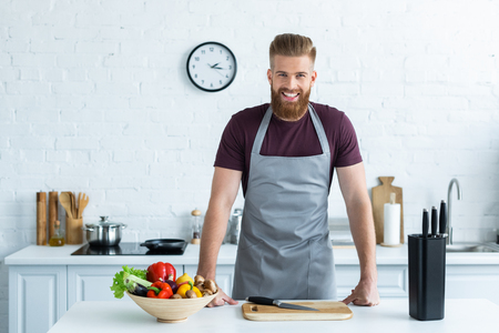 Foto de handsome bearded young man in apron smiling at camera while cooking in kitchen - Imagen libre de derechos