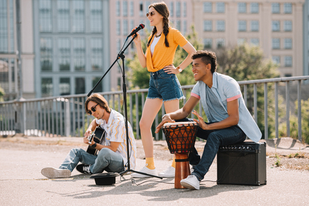 Photo for Team of young friends performing and singing in urban environment - Royalty Free Image