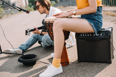 Photo for Woman with djembe and man with guitar performing on sunny city street - Royalty Free Image