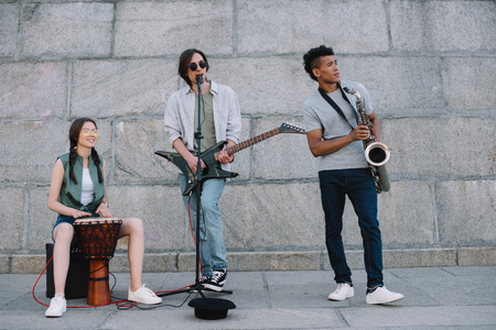 Photo for Multiracial young people performing in band on street - Royalty Free Image