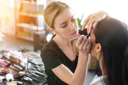 Photo for side view of focused makeup artist applying eye shadows on womans eyelid - Royalty Free Image