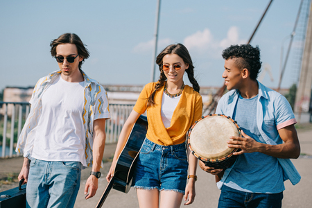 Photo for Young and happy street musicians carrying instruments in city - Royalty Free Image